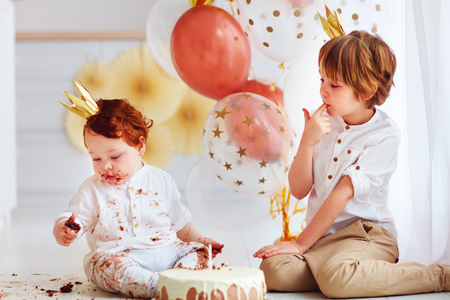 cute kids, brothers tasting birthday cake on 1st birthday party Stock Photo