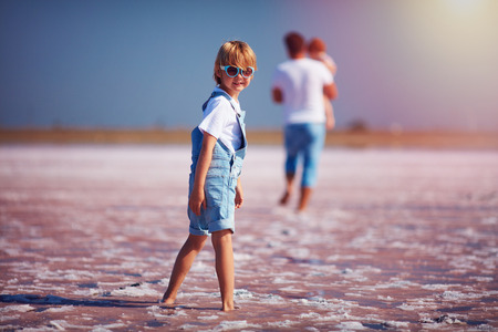 Young boy in jeans romper and sunglasses walking through the pink salt lake