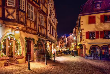 tradizionali case a graticcio sulla strada naroow di Kaysersberg, in Alsazia, in Francia, alla vigilia di Natale Archivio Fotografico