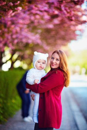 portrait of young woman, happy mother with cute infant baby in arm, on the walk in spring city