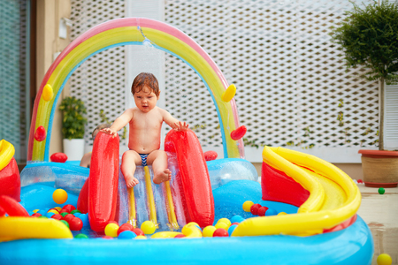 infant baby boy are going to slide in inflatable pool at the patio zone Stock Photo