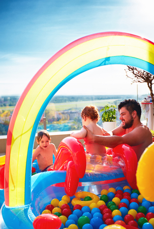 family having fun in inlatable pool with slide and lots of colorful balls