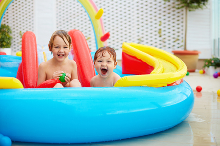 excited kids, family having fun in colorful inflatable pool on patio Stock Photo