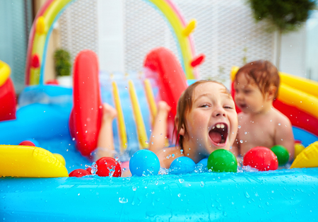 excited kids having fun in colorful inflatable pool on patio. Focus on water splash
