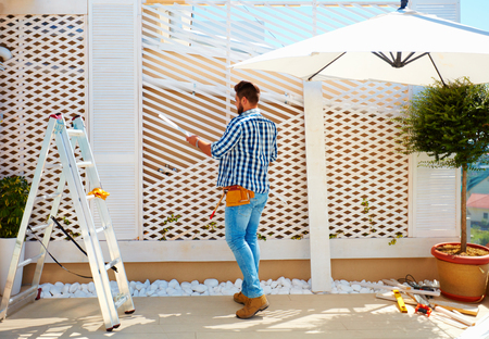 young adult man building wooden pergola wall on rooftop patio zone