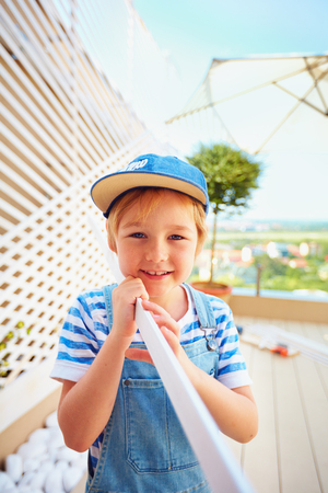 cute young boy, kid halps father with renovation of wodden pergola wall on rooftop patio zone