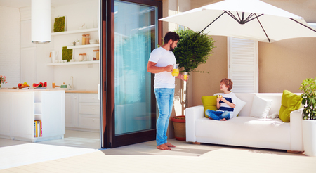 father and son, family relaxing on rooftop patio with open space kitchen at warm summer day