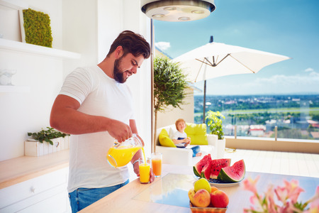 young adult man, father pouring fresh juice while standing in open space kitchen on a sunny summer day