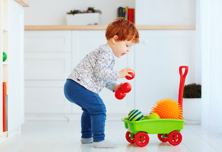 cute redhead toddler baby collecting different balls into toy pushcart Stock Photo
