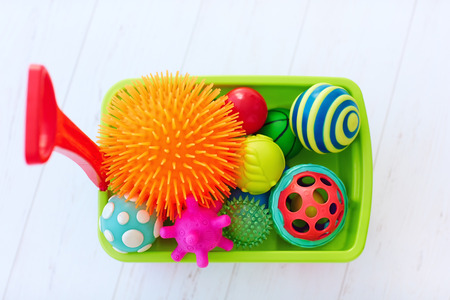colorful toy trolley full of vibrant and various shape tactile balls for kid's development Stock Photo - 94311163