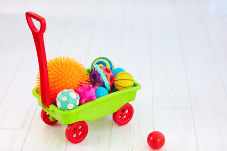 colorful toy trolley full of different color and shape tactile balls for kid's development Stock Photo