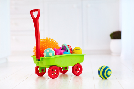 colorful toy trolley full of different color and shape tactile balls for kids development Stock Photo
