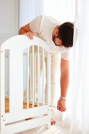 father installing the crib, preparing for a new baby in the family Stok Fotoğraf