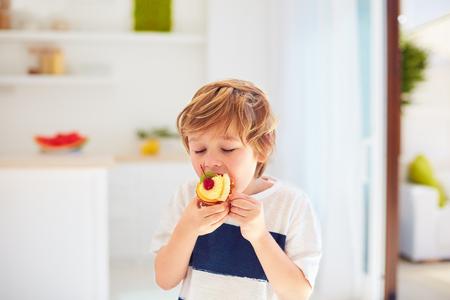 かわいい子供、自宅でホイップクリームとフルーツとおいしいカップケーキを食べる若い男の子