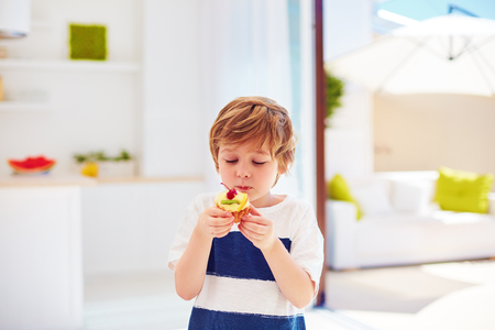 cute kid, young boy eating tasty cupcake with whipped cream and fruits at home