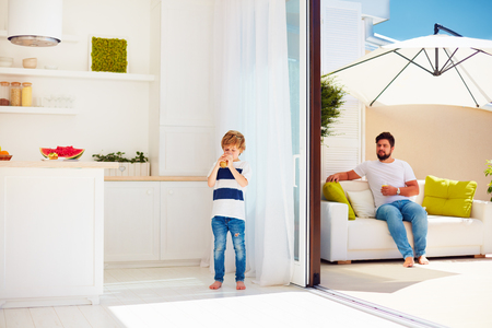 happy family relaxing on rooftop patio with open space kitchen at warm summer day