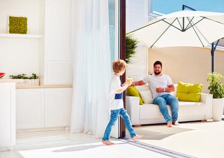 glückliche Familie, die auf Dachspitzenterrasse mit offener Raumküche am warmen Sommertag sich entspannt