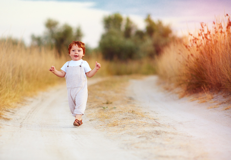 adorable redhead toddler baby boy in jumpsuit running along rural summer road in sunburned field