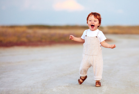 adorable redhead toddler baby boy in jumpsuit running through the summer road and field