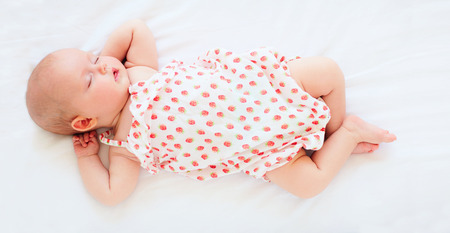 cute infant baby girl in bodysuit sleeping in bed. top view Banco de Imagens