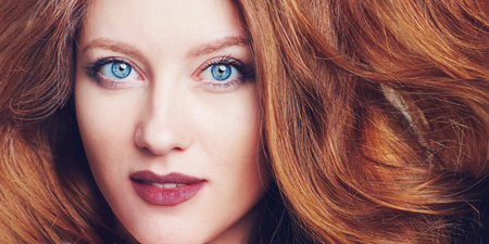 Portrait of beautiful young woman with big blue eyes, berry lips and brazen hair