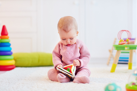 cute little baby girl sitting on the carpet among the development toys, with her first book