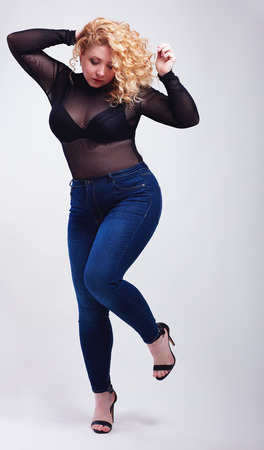 plus size young woman in jeans and transparent bodysuit