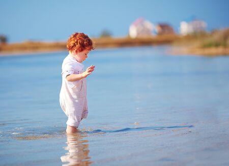 cute redhead toddler baby boy walking in water at summer lake coast