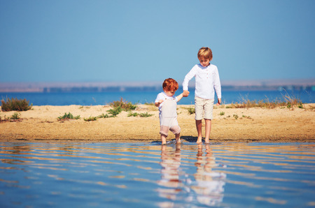 young kids, brothers walking in shallow water in the summer morning