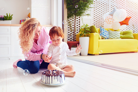 happy mother and toddler son poking fingers in birthday cake