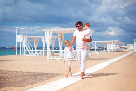 happy father and sons walking on sandy beach, summer vacation in tropical resort