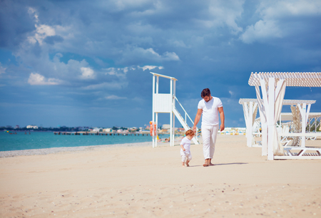 happy father and son walking on sandy beach, summer vacation