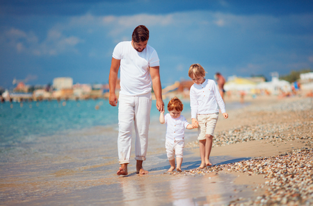 happy family enjoys summer vacation on azure coast, walking together in the surf