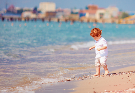 cute redhead toddler baby walking along the summer beach