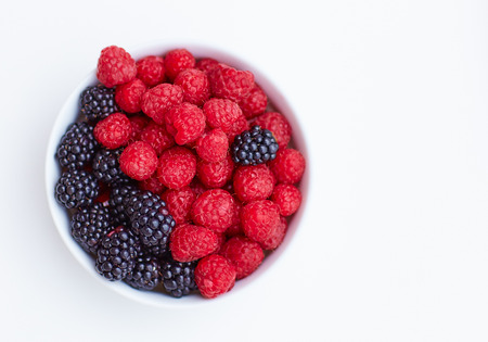 top view on plate with fresh and ripe raspberries and blackberries on white