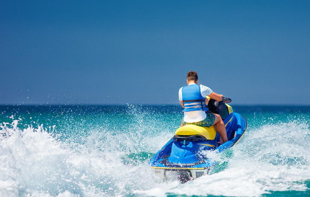 young adult man running the wave on jet ski during summer vacation 스톡 콘텐츠