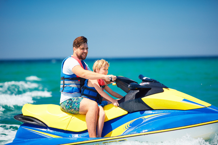 happy, excited family, father and son having fun on jet ski at summer vacation Фото со стока - 105349448