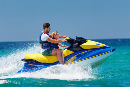 happy, excited family, father and son having fun on jet ski at summer vacation Фото со стока - 105349449