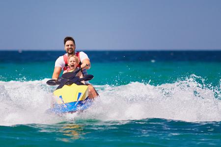 Familia feliz y emocionada, padre e hijo divirtiéndose en jet ski en las vacaciones de verano