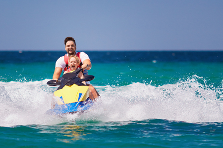 happy, excited family, father and son having fun on jet ski at summer vacation Archivio Fotografico - 105349453