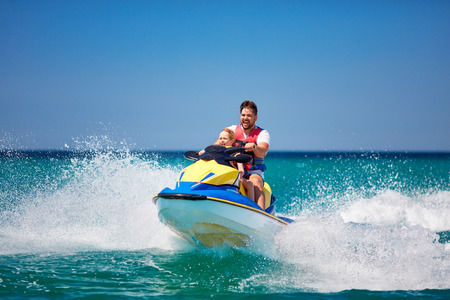 happy, excited family, father and son having fun on jet ski at summer vacation Фото со стока - 105349455