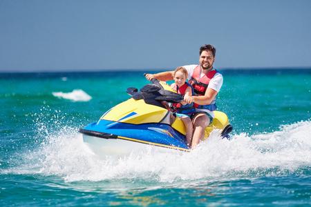 gelukkige, opgewonden familie, vader en zoon met plezier op jetski op zomervakantie