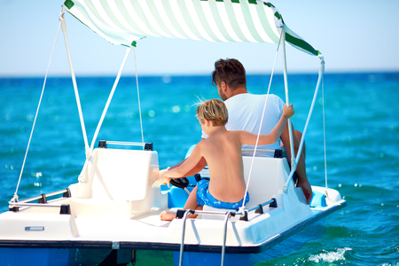 happy family, father and son enjoy sea adventure on watercraft catamaran at summer vacation Imagens - 104694643