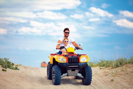 famiglia felice, padre e figlio in sella a un quad atv sulla spiaggia sabbiosa