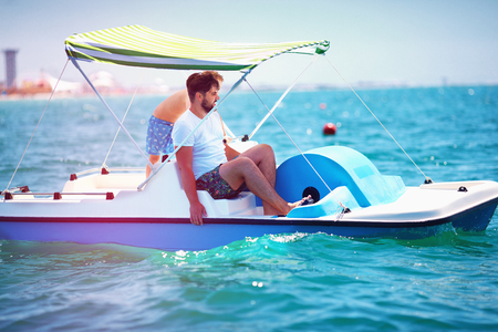 happy family, father and son enjoy sea adventure on watercraft catamaran at summer vacation