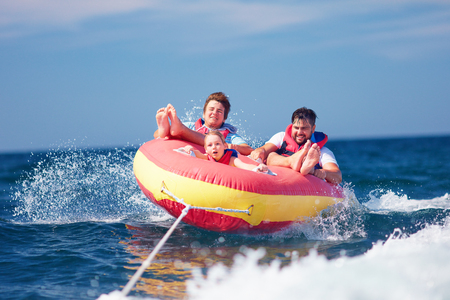 excited friends, family having fun, riding on water tube during summer vacation
