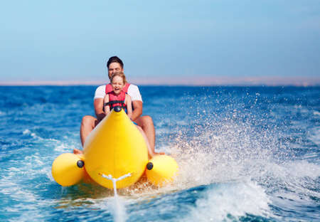 happy family, delighted father and son having fun, riding on banana boat during summer vacation Stok Fotoğraf