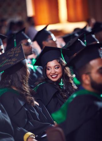 Groupe d'étudiants diplômés heureux en robes sur la cérémonie de remise des diplômes