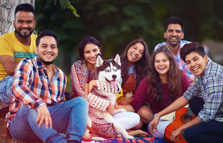 portrait of happy friends chilling together with pet dog in park