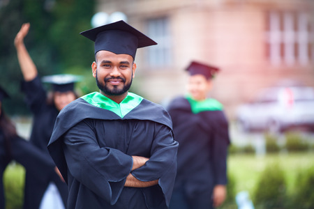 portrait of successful indian student in graduation gown Stockfoto